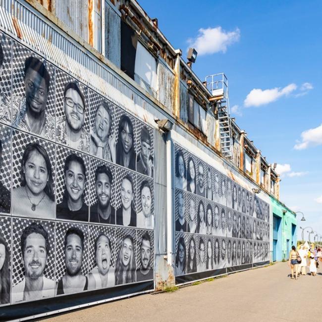 """Des portraits viennent d'apparaître au cœur du Vieux-Port. Les avez-vous vus ? Ce sont """"Les Visages de Montréal"""", une action de groupe du Inside Out Project de l'artiste français JR, qui est déployée à travers plusieurs quartiers de Montréal. À travers cette œuvre publique, le Vieux-Port met en lumière les visages souriants de toutes les personnes qui le font vivre, aussi bien ses visiteurs que ses commerçants·es, résidents·es et employés·es. Célébrons les Montréalais·es et leur résilience! 📷 Eva Blue ---------- A series of portraits have just appeared at the Old Port. Have you seen them? """"Les Visages de Montréal / Faces of Montréal"""" is a collective art initiative led by French artist JR as part of the Inside Out Project. You'll see it in different neighbourhoods across the city. Thanks to this work of public art, the Old Port now celebrates the smiling faces of all those who bring it to life, from visitors and merchants to residents and employees. Let's celebrate Montréalers and their resilience! 📷 Eva Blue ------ #vieuxportmtl #oldportmtl @montreal @montrealcentreville #exploremontreal #514  #coeurdelilemtl #coeurdelile #mtl #yul #montreal #mtlblog #livemontreal #mtlmoments #montréaljetaime #arts #artmtl #tourismelocal #summervibe #bonjourquebec #mtlphoto #mtllife  #visagesmtl"""